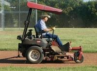 Man on a Riding Mower Maintaining a Ball Field